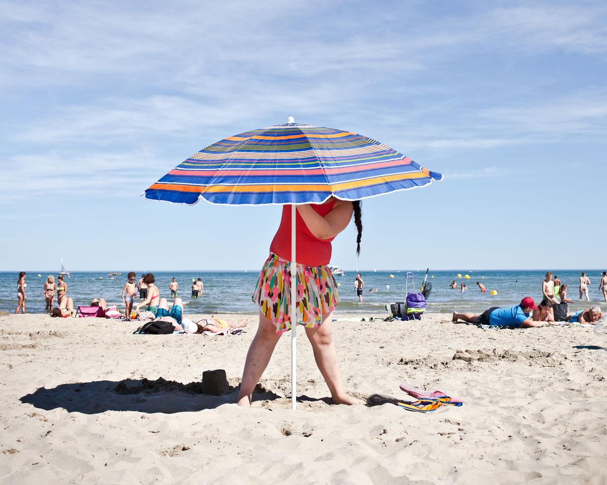Maddelena installe un parasol sur la plage de Palavas-les-Flots. Ses parents n'étant pas motorisés. ©Sandra Mehl